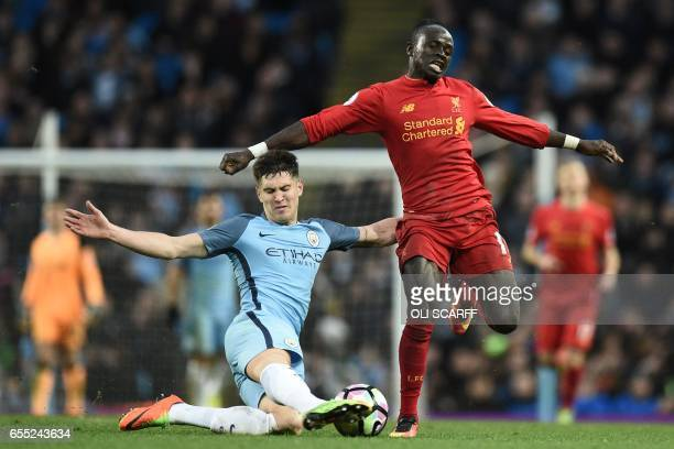 TOPSHOT Liverpool's Senegalese midfielder Sadio Mane is tackled by Manchester City's English defender John Stones during the English Premier League...