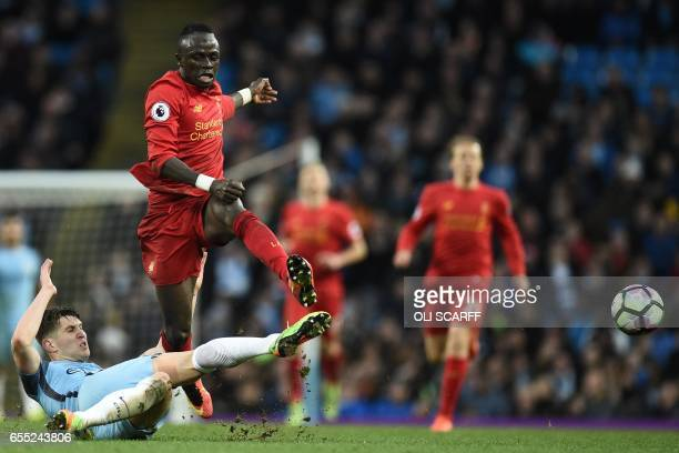 Liverpool's Senegalese midfielder Sadio Mane is tackled by Manchester City's English defender John Stones during the English Premier League football...