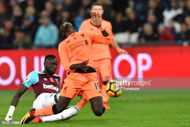 Liverpool's Senegalese midfielder Sadio Mane is tackled by West Ham United's Senegalese midfielder Cheikhou Kouyate during the English Premier League...