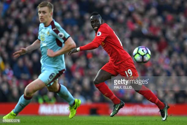 Liverpool's Senegalese midfielder Sadio Mane vies with Burnley's English defender Ben Mee during the English Premier League football match between...