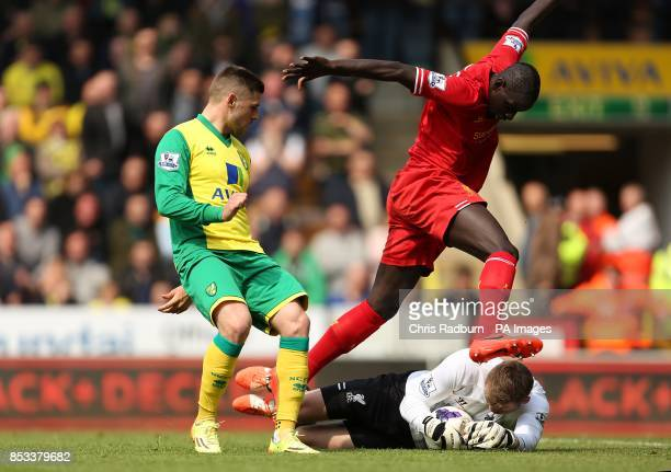 Liverpool's Simon Mignolet saves at the feet of team mate Mamadou Sakho and Norwich City's Gary Hooper