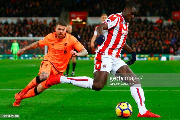 Liverpool's Spanish defender Alberto Moreno vies with Stoke City's French defender Kurt Zouma during the English Premier League football match...