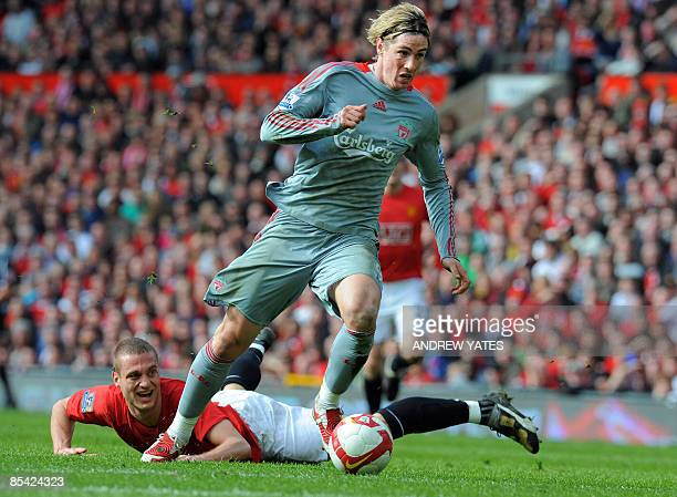 Liverpool's Spanish forward Fernando Torres beats Manchester United's Serbian defender Nemanja Vidic to score the equalising goal during their...
