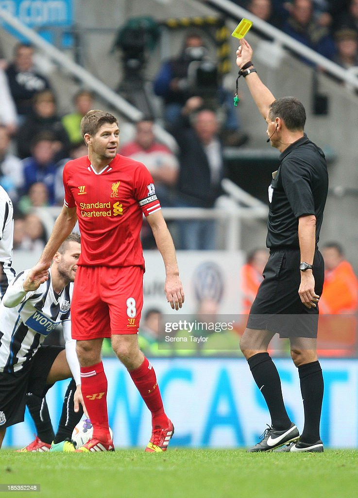 Liverpool's Steven Gerrard (C) receives a yellow card from referee Andre Marriner during the Barclays Premier League match between Newcastle United and Liverpool at St. James Park on October 19, 2013, in Newcastle upon Tyne, England.