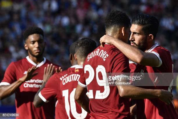 Liverpool's Team players celebrate with Liverpool's English striker Dominic Solanke after he scored 01 during a friendly football match Hertha Berlin...