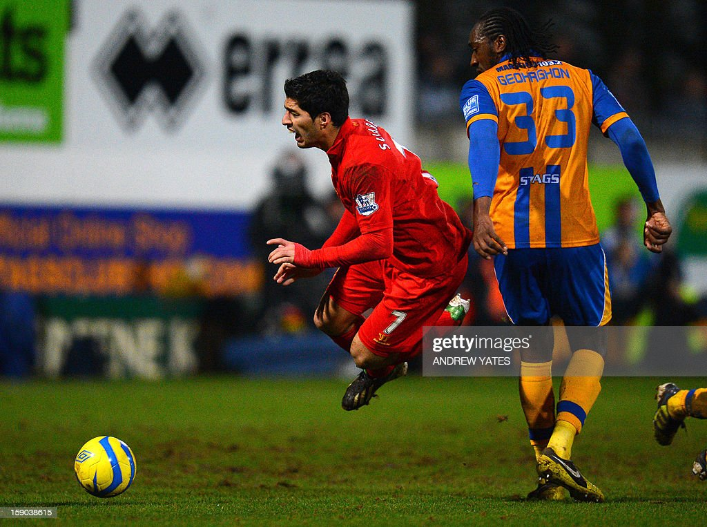 "Liverpool's Uruguayan forward Luis Suarez (L) is fouled by Mansfield Town's English defender Exodus Geohaghon during the FA Cup third round football match between Mansfield Town and Liverpool at Field Mill in Mansfield, central England, on January 6, 2013. Liverpool won the match 2-1. USE. No use with unauthorized audio, video, data, fixture lists, club/league logos or ""live"" services. Online in-match use limited to 45 images, no video emulation. No use in betting, games or single club/league/player publications."