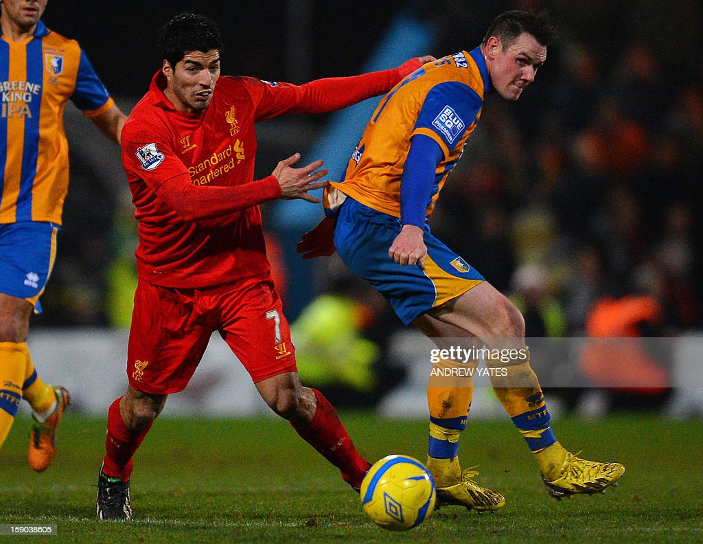 "Liverpool's Uruguayan forward Luis Suarez (L) vies with Mansfield Town's Welsh defender Lee Beevers during the FA Cup third round football match between Mansfield Town and Liverpool at Field Mill in Mansfield, central England, on January 6, 2013. Liverpool won the match 2-1. USE. No use with unauthorized audio, video, data, fixture lists, club/league logos or ""live"" services. Online in-match use limited to 45 images, no video emulation. No use in betting, games or single club/league/player publications."