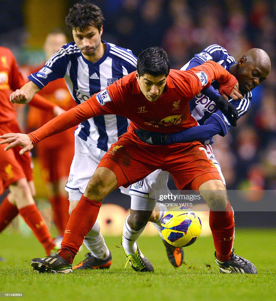 "Liverpool's Uruguayan forward Luis Suarez (C) vies with West Bromwich Albion's Congolese defender Youssuf Mulumbu (R) and West Bromwich Albion's Argentine midfielder Claudio Yacob during the English Premier League football match between Liverpool and West Bromwich Albion at Anfield in Liverpool, northwest England on February 11, 2013. West Bromwich won the match 2-0. AFP PHOTO/ANDREW YATES === RESTRICTED TO EDITORIAL USE. No use with unauthorized audio, video, data, fixture lists, club/league logos or ""live"" services. Online in-match use limited to 45 images, no video emulation. No use in betting, games or single club/league/player publications ==="