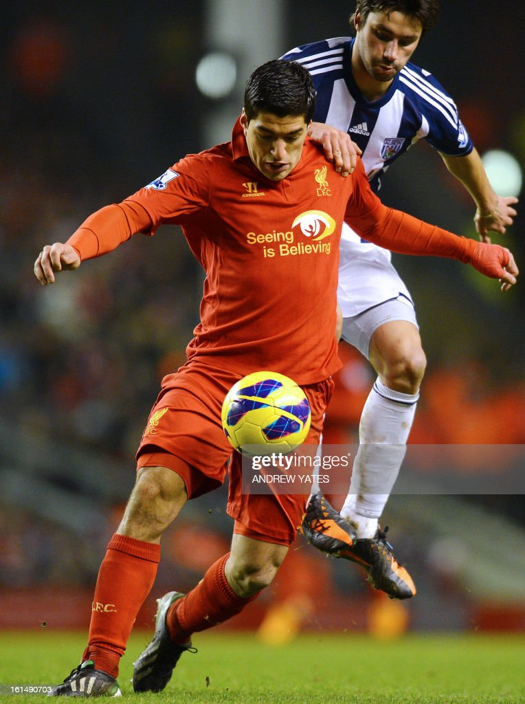 """Liverpool's Uruguayan forward Luis Suarez (L) vies with West Bromwich Albion's Argentine midfielder Claudio Yacob during the English Premier League football match between Liverpool and West Bromwich Albion at Anfield in Liverpool, northwest England on February 11, 2013. West Bromwich won the match 2-0. AFP PHOTO/ANDREW YATES === RESTRICTED TO EDITORIAL USE. No use with unauthorized audio, video, data, fixture lists, club/league logos or """"live"""" services. Online in-match use limited to 45 images, no video emulation. No use in betting, games or single club/league/player publications ==="""