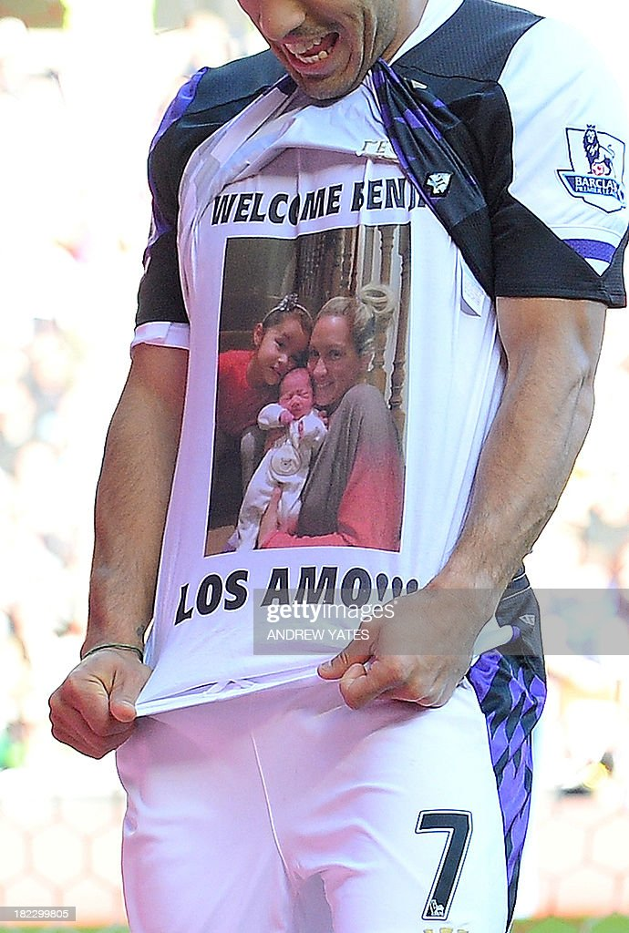 Liverpool's Uruguayan striker Luis Suarez celebrates pulling up his jersey to reveal a printed picture on his T-shirt of his family, wife Sofia, daughter Delfina and new-born second child, with the inscription 'welcome Benja - los amo (I love them)' after scoring his team's second goal during the English Premier League football match between Sunderland and Liverpool at the Stadium of Light in Sunderland, northeast England, on September 29, 2013. AFP PHOTO / ANDREW YATES USE. No use with unauthorized audio, video, data, fixture lists, club/league logos or live services. Online in-match use limited to 45 images, no video emulation. No use in betting, games or single club/league/player publications.