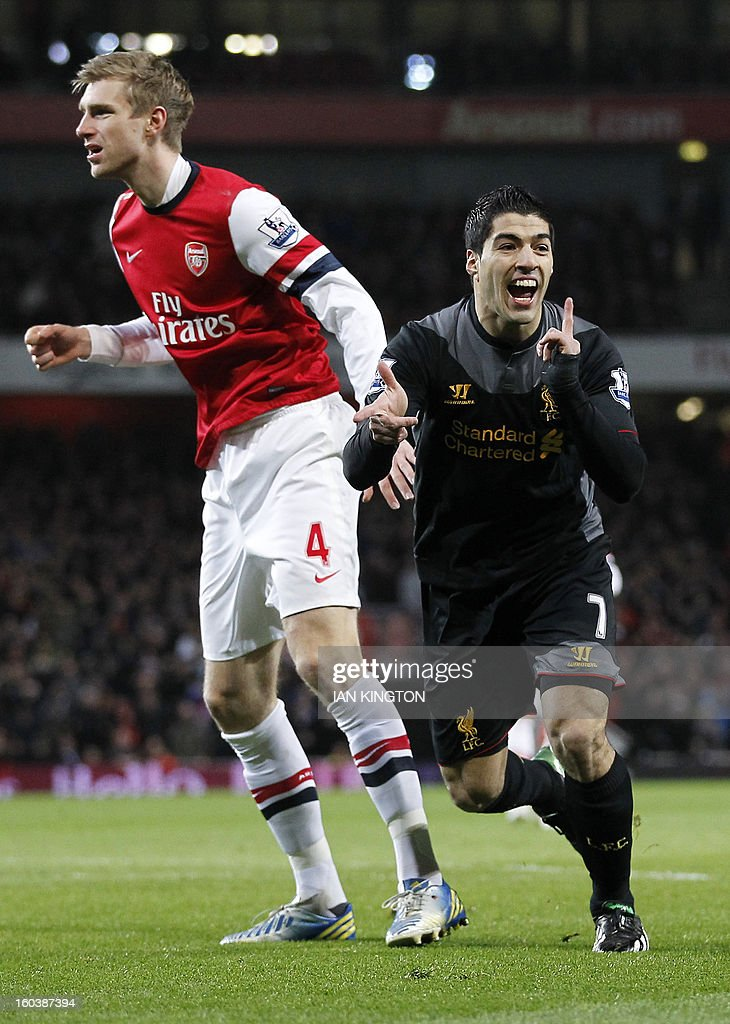 """Liverpool's Uruguayan striker Luis Suarez (R) celebrates scoring the first goal as Arsenal's German defender Per Mertesacker (L) reacts during the English Premier League football match between Arsenal and Liverpool at The Emirates Stadium in north London on January 30, 2013. USE. No use with unauthorized audio, video, data, fixture lists, club/league logos or """"live"""" services. Online in-match use limited to 45 images, no video emulation. No use in betting, games or single club/league/player publications."""
