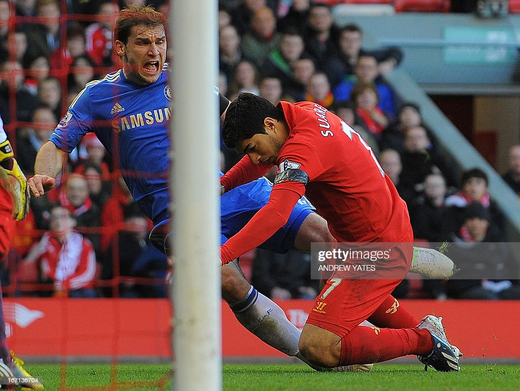 """Liverpool's Uruguayan striker Luis Suarez (R) clashes with Chelsea's Serbian defender Branislav Ivanovic (L) after appearing to bite the Chelsea player during the English Premier League football match between Liverpool and Chelsea at the Anfield stadium in Liverpool, northwest England, on April 21, 2013. USE. No use with unauthorized audio, video, data, fixture lists, club/league logos or """"live"""" services. Online in-match use limited to 45 images, no video emulation. No use in betting, games or single club/league/player publications."""