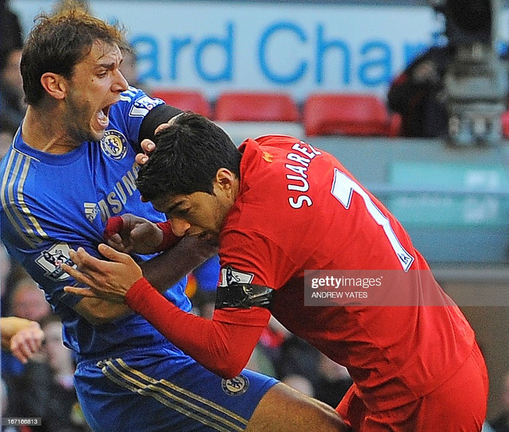 """Liverpool's Uruguayan striker Luis Suarez (R) clashes with Chelsea's Serbian defender Branislav Ivanovic (L) after appearing to bite the Chelsea player during the English Premier League football match between Liverpool and Chelsea at the Anfield stadium in Liverpool, northwest England, on April 21, 2013. Liverpool striker Luis Suarez on April 21 apologised for biting Chelsea defender Branislav Ivanovic during the sides' 2-2 Premier League draw at Anfield. The incident occurred mid-way through the second half, with Liverpool trailing 2-1 following a tussle in the penalty area. AFP PHOTO / ANDREW YATES USE. No use with unauthorized audio, video, data, fixture lists, club/league logos or """"live"""" services. Online in-match use limited to 45 images, no video emulation. No use in betting, games or single club/league/player publications."""