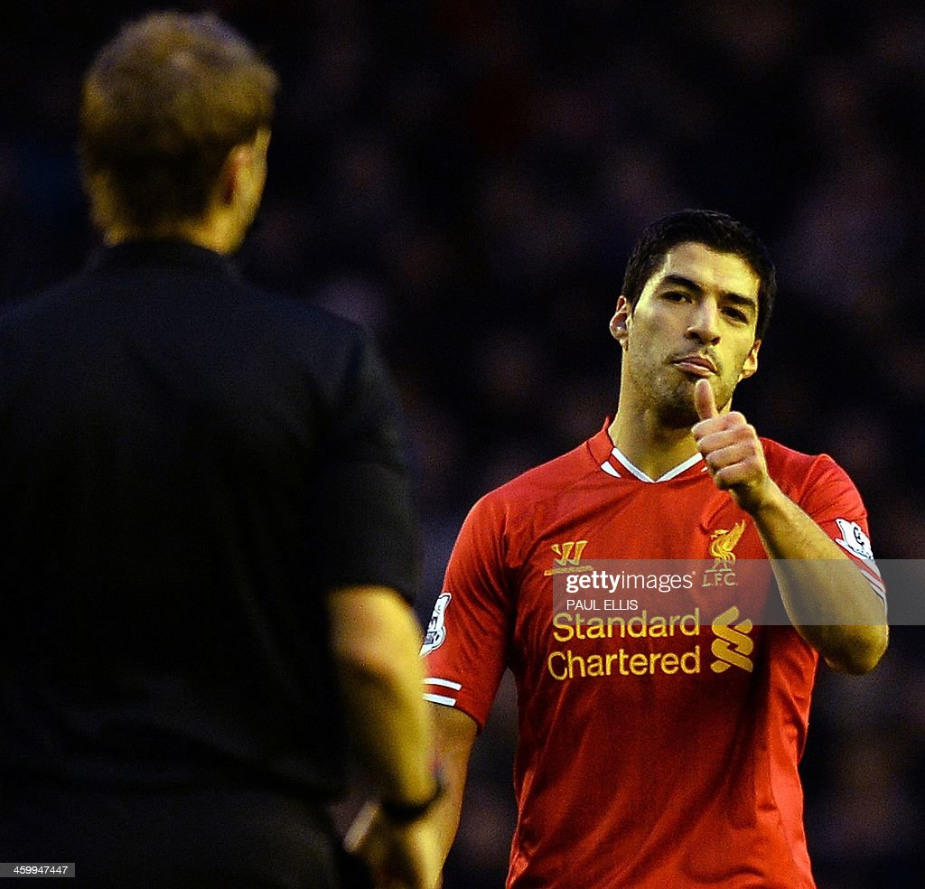 Liverpool's Uruguayan striker Luis Suarez (R) gestures to referee Craig Pawson (L) as he is booked during the English Premier League football match between Liverpool and Hull City at Anfield in Liverpool, northwest England, on January 1, 2014. USE. No use with unauthorized audio, video, data, fixture lists, club/league logos or live services. Online in-match use limited to 45 images, no video emulation. No use in betting, games or single club/league/player publications.