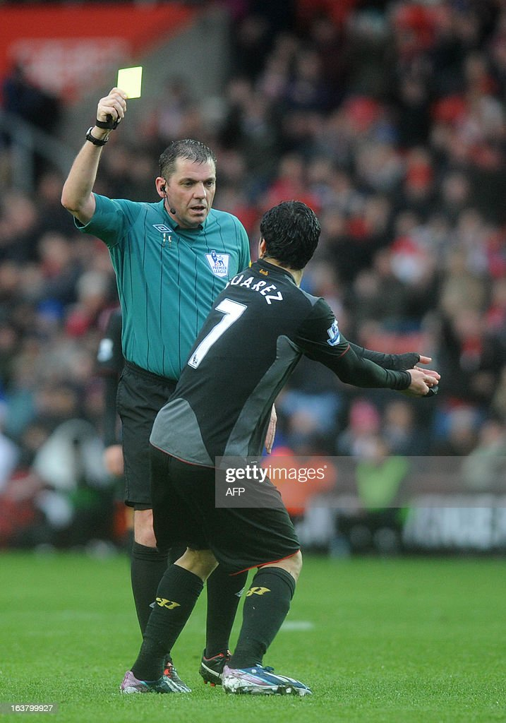 "Liverpool's Uruguayan striker Luis Suarez (R) is booked by referee Phil Dowd during the Barclays Premier League football match between Southampton and Liverpool at St Mary's Stadium in Southampton on March 16, 2013. Southampton won 3-1. AFP PHOTO/Olly Greenwood USE. No use with unauthorized audio, video, data, fixture lists, club/league logos or ""live"" services. Online in-match use limited to 45 images, no video emulation. No use in betting, games or single club/league/player publications.7 2981656. Do not alter/modify photo."