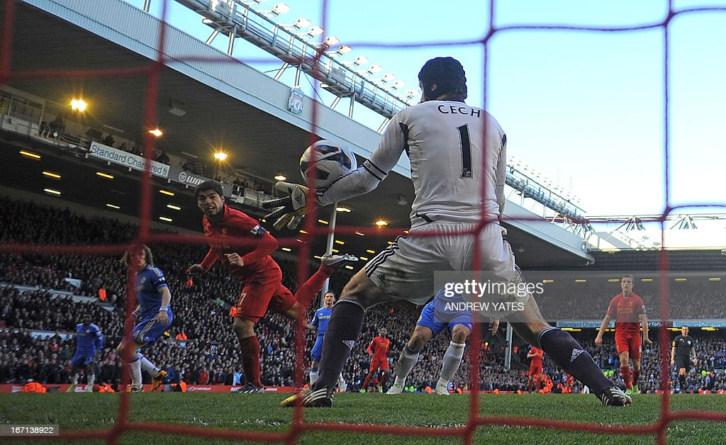"Liverpool's Uruguayan striker Luis Suarez (2nd L) scores their late equalizer past Chelsea's Czech goalkeeper Petr Cech (R) during the English Premier League football match between Liverpool and Chelsea at the Anfield stadium in Liverpool, northwest England, on April 21, 2013. The game finished 2-2. AFP PHOTO / ANDREW YATES USE. No use with unauthorized audio, video, data, fixture lists, club/league logos or ""live"" services. Online in-match use limited to 45 images, no video emulation. No use in betting, games or single club/league/player publications."