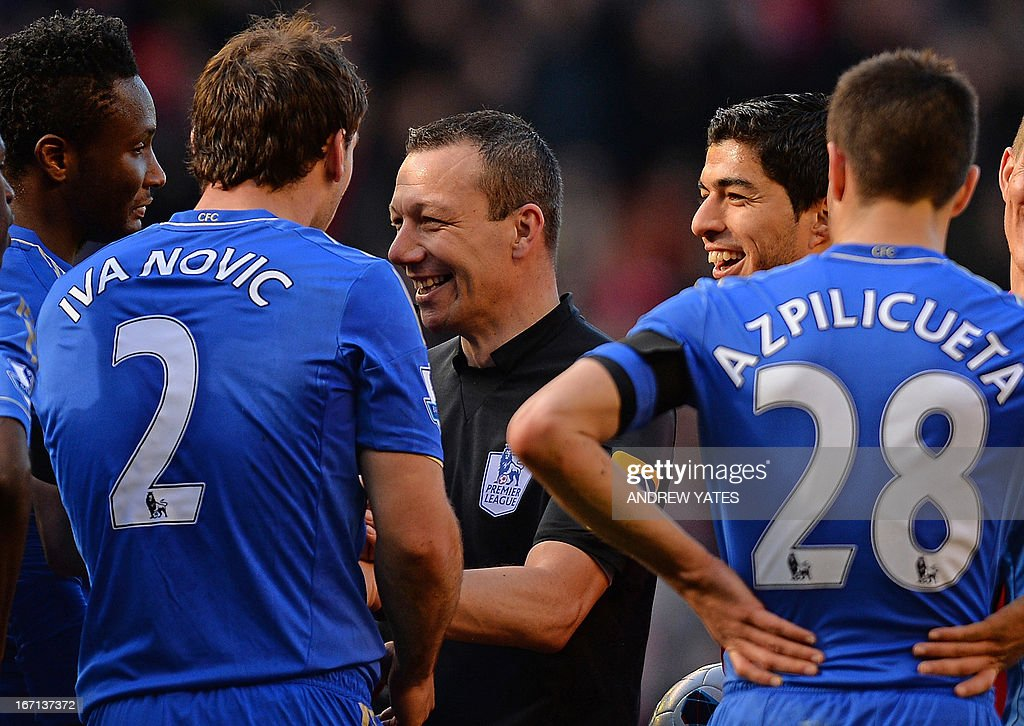 "Liverpool's Uruguayan striker Luis Suarez (2nd R) smiles as Chelsea's Serbian defender Branislav Ivanovic (L) complains to referee Kevin Friend (2nd L) about being bitten by him during the English Premier League football match between Liverpool and Chelsea at the Anfield stadium in Liverpool, northwest England, on April 21, 2013. The game finished 2-2. USE. No use with unauthorized audio, video, data, fixture lists, club/league logos or ""live"" services. Online in-match use limited to 45 images, no video emulation. No use in betting, games or single club/league/player publications."