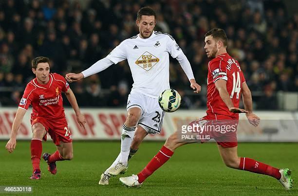 Liverpool's Welsh midfielder Joe Allen and Liverpool's English midfielder Jordan Henderson vie with Swansea City's Icelandic midfielder Gylfi...