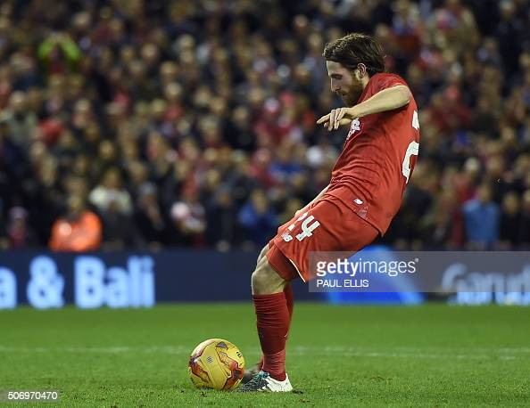 Liverpool's Welsh midfielder Joe Allen scores the winning penalty in the shootout after the English League Cup semifinal second leg football match...