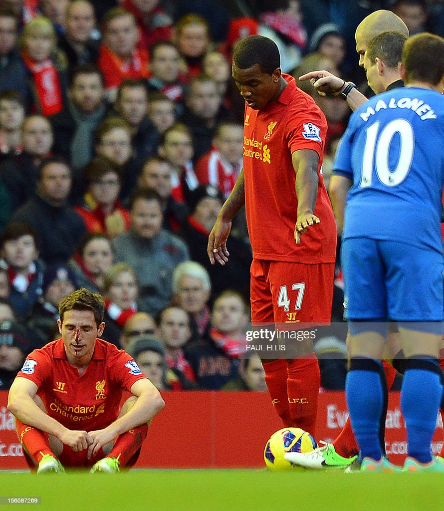 """Liverpool's Welsh midfielder Joe Allen (L) sits after picking up an injury during the English Premier League football match between Liverpool and Wigan Athletic at Anfield in Liverpool, north-west England on November 17, 2012. Liverpool won the game 3-0. USE. No use with unauthorized audio, video, data, fixture lists, club/league logos or """"live"""" services. Online in-match use limited to 45 images, no video emulation. No use in betting, games or single club/league/player publications."""