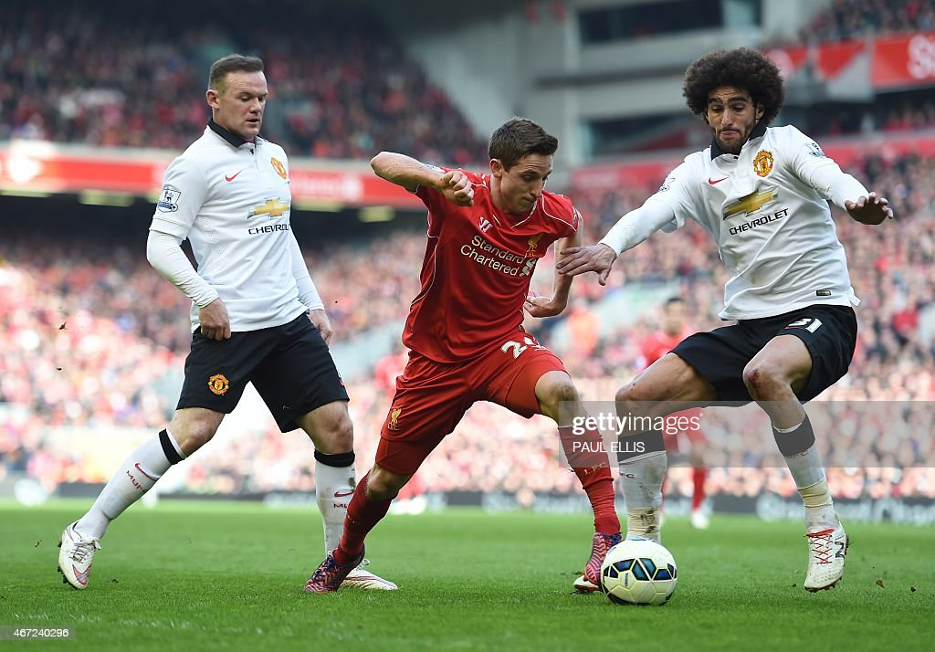 Liverpool's Welsh midfielder <a gi-track='captionPersonalityLinkClicked' href=/galleries/search?phrase=Joe+Allen+-+Welsh+Soccer+Player&family=editorial&specificpeople=9629091 ng-click='$event.stopPropagation()'>Joe Allen</a> vies with Manchester United's English striker <a gi-track='captionPersonalityLinkClicked' href=/galleries/search?phrase=Wayne+Rooney&family=editorial&specificpeople=157598 ng-click='$event.stopPropagation()'>Wayne Rooney</a> (L) and Manchester United's Belgian midfielder <a gi-track='captionPersonalityLinkClicked' href=/galleries/search?phrase=Marouane+Fellaini&family=editorial&specificpeople=3936316 ng-click='$event.stopPropagation()'>Marouane Fellaini</a> (R) during the English Premier League football match between Liverpool and Manchester United at Anfield in Liverpool, north west England on March 22, 2015.