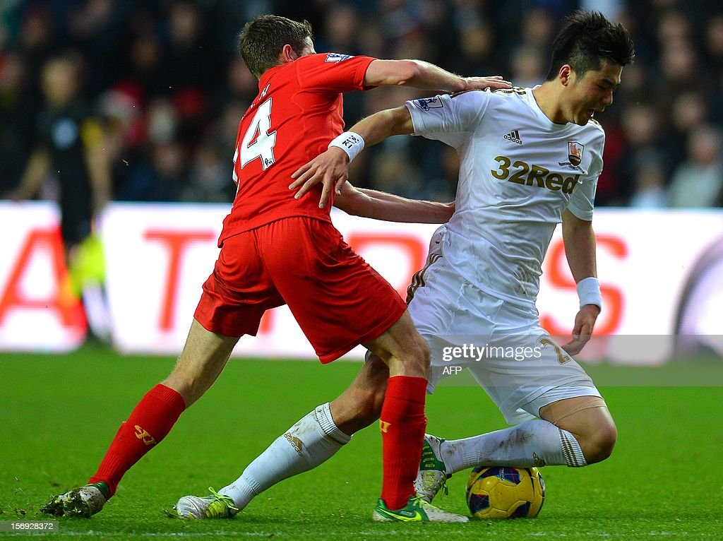 """Liverpool's Welsh midfielder Joe Allen (L) vies with Swansea City's South Korean midfielder Ki Sung-Yueng during the English Premier League football match between Swansea City and Liverpool at The Liberty stadium in Swansea, south Wales on November 25, 2012. AFP PHOTO/ANDREW YATES. RESTRICTED TO EDITORIAL USE. No use with unauthorized audio, video, data, fixture lists, club/league logos or """"live"""" services. Online in-match use limited to 45 images, no video emulation. No use in betting, games or single club/league/player publications."""