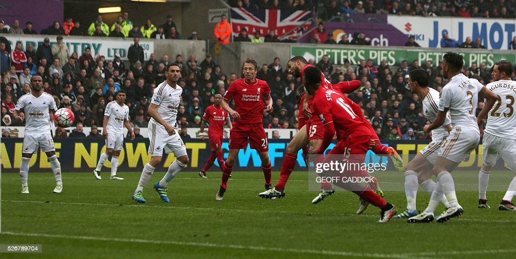 Liverpools Zaire-born Belgian striker Christian Benteke (C obscured) scores their first goal during the English Premier League football match between Swansea City and Liverpool at the Liberty Stadium, in Swansea, South Wales, on May 1, 2016. / AFP / GEOFF CADDICK / RESTRICTED TO EDITORIAL USE. No use with unauthorized audio, video, data, fixture lists, club/league logos or 'live' services. Online in-match use limited to 75 images, no video emulation. No use in betting, games or single club/league/player publications. /