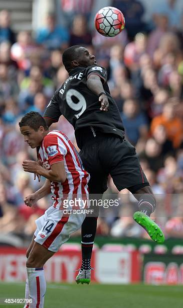 Liverpool's Zaireborn Belgian striker Christian Benteke vies with Stoke City's Dutch midfielder Ibrahim Afellay during the English Premier League...