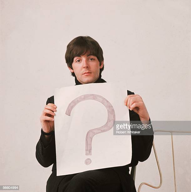 Liverpudlian pop star Paul McCartney of The Beatles holds up a large piece of paper with a question mark 1965