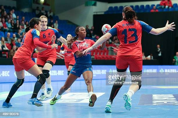 Livia Veranes Mustelier of Cuba is passing the ball against Cristina Neagu and Luciana Marin of Romania during the game between Romania and Cuba of...