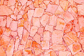 Closeup of trendy coloured living coral, orange and pink abstract sandstone mosaic wall. For pattern, texture and background your concept or product