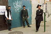 Three Hasidic Men Hanging Out Together on a Sidewalk in Williamsburg Brooklyn NYC USA in front of a wooden wall