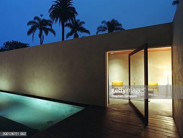 Living room and lap pool of modern house, nighttime