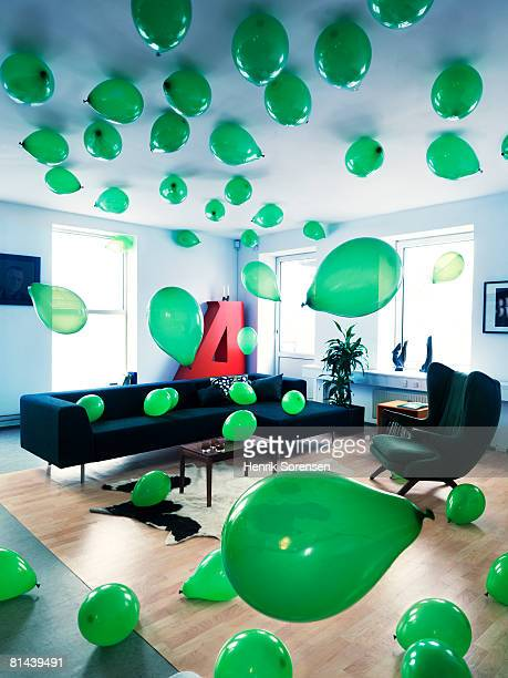 Living room filled with green balloons.