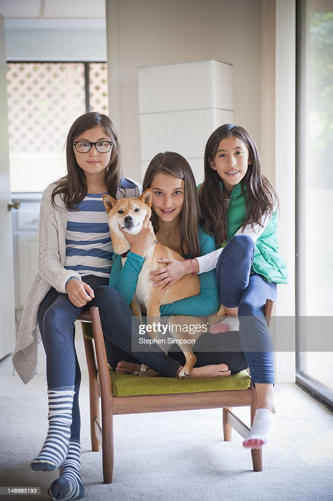 living room portrait, 3 sisters with their dog : Stock Photo