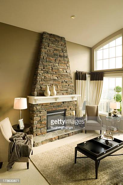 A living room stone fireplace in a beautiful mansion