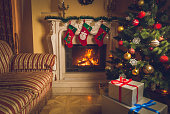 Toned interior image of living room with burning fireplace, decorated Christmas tree and stack of gifts