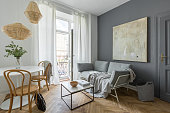 Gray living room with couch, table, modern painting and balcony