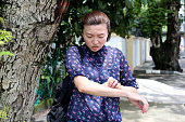 A lady cannot stop from rubbing her hand itchiness.