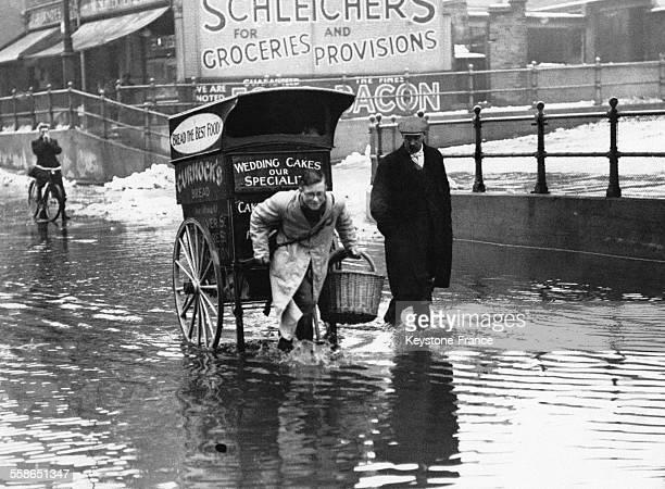 Livreur de pâtisseries bravant les inondations et tirant avec difficulté son chariot à Londres RoyaumeUni le 26 janvier 1939