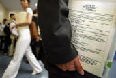 LiYang Lin holds his resume at the Asian Diversity Career Expo May 13 2004 in New York City The third job fair for Asian Americans included...