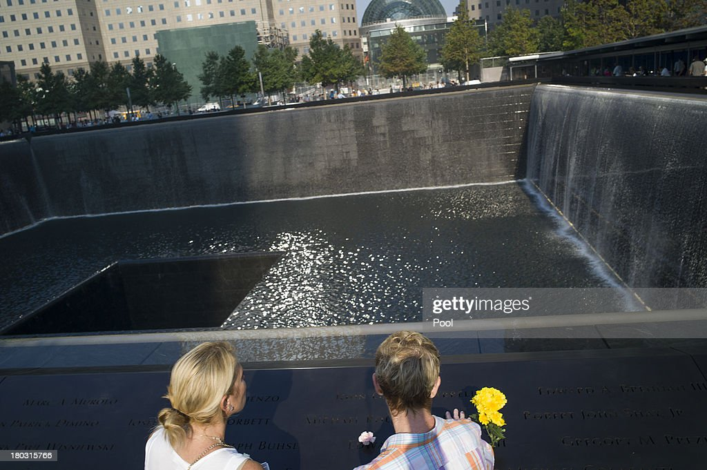 Liz Breslin (L) and Mary Beth Andrews stand by the inscription of Breslin's boyfriend and Andrews's brother Cantor Fitzgerald employee Michael Rourke Andrews at the 9/11 Memorial before ceremonies for the 12th anniversary of the terrorist attacks on lower Manhattan at the World Trade Center site on September 11, 2013 in New York City. The nation is commemorating the anniversary of the 2001 attacks, which resulted in the deaths of nearly 3,000 people after two hijacked planes crashed into the World Trade Center, one into the Pentagon in Arlington, Virginia and one crash landed in Shanksville, Pennsylvania. Following the attacks in New York, the former location of the Twin Towers has been turned into the National September 11 Memorial & Museum.