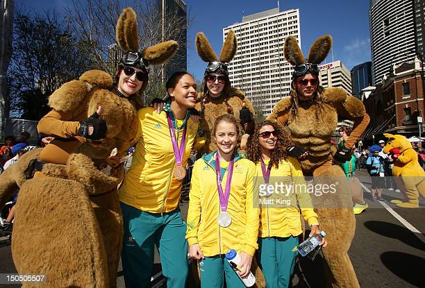 Liz Cambridge Brittany Broben and Jessica Fox pose with performers during the Australian Olympic Team Homecoming Parade in the Sydney CBD on August...