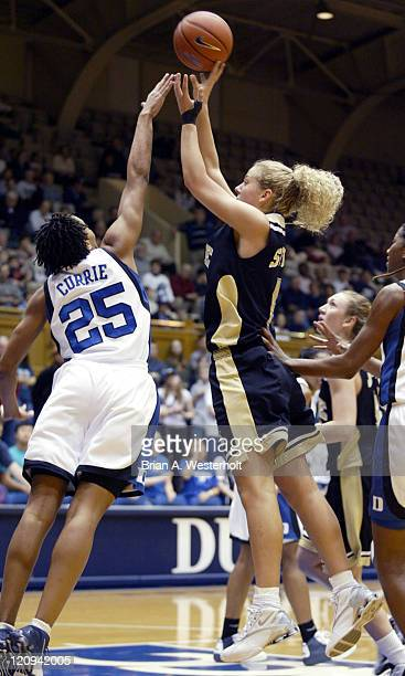 Liz Strunk shoots over the outstretched hand of Monique Currie during first half action February 12 2004