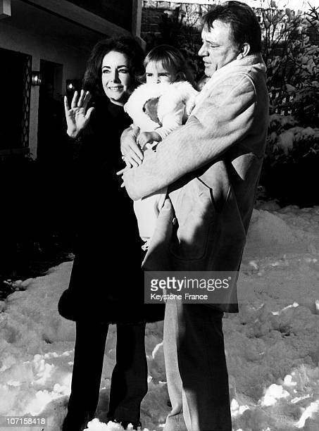 Liz Taylor and Richard Burton carrying in his arms the granddaughter of actress Sandra Wilding in the seventies
