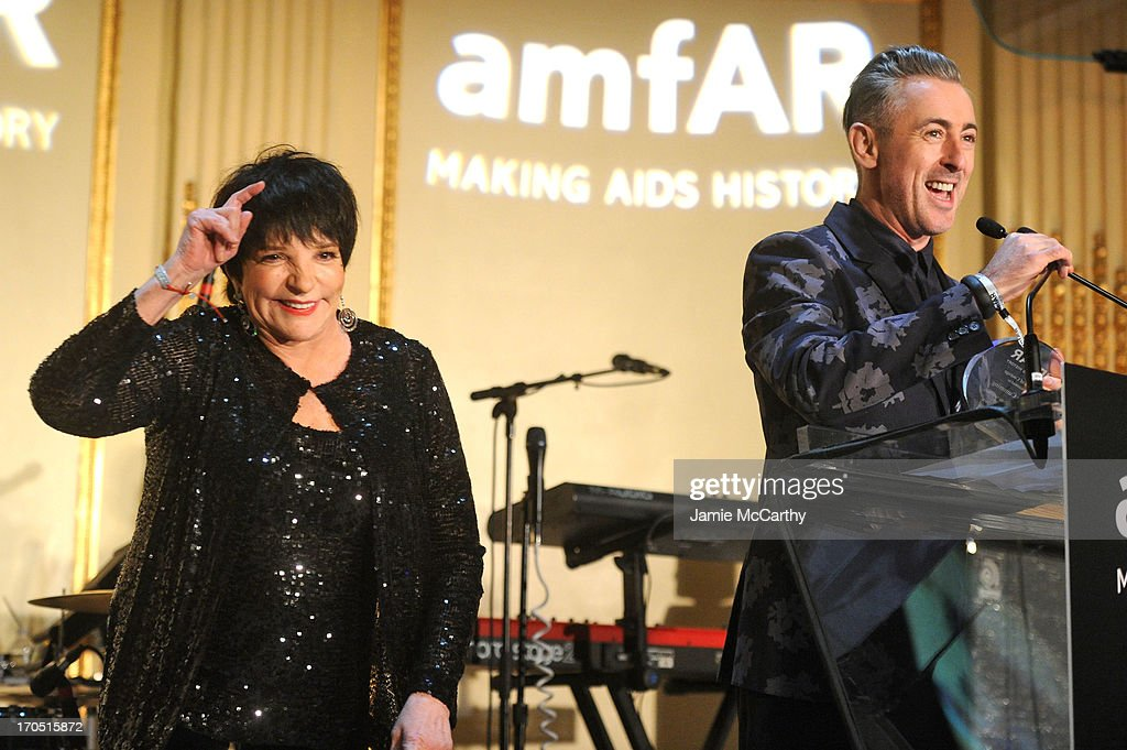 Liza Minelli (L) and Alan Cumming recipient of the Award of Courage speak on stage during the 4th Annual amfAR Inspiration Gala New York at The Plaza Hotel on June 13, 2013 in New York City.