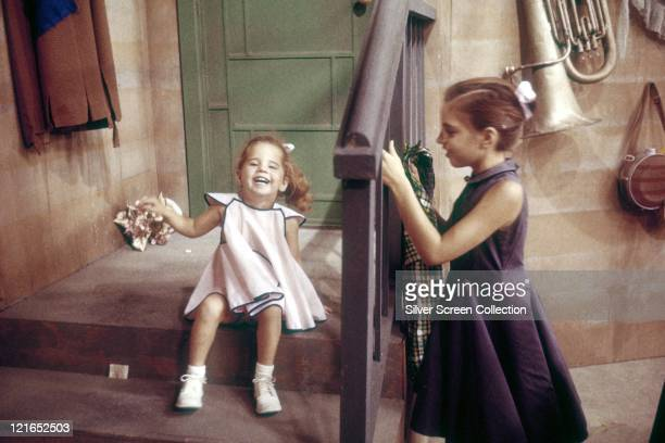 Liza Minnelli US actress and singer as a child sitting on a step and holding a posy of flowers with an older child standing against the railings to...