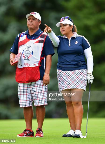 Lizette Salas of Team USA and caddie discuss a shot on the 18th hole during the final day singles matches of The Solheim Cup at Des Moines Golf and...