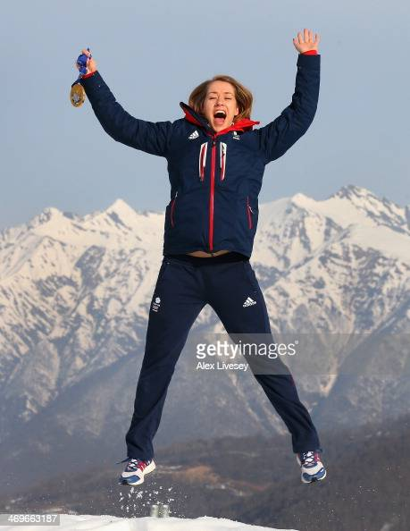 Lizzy Yarnold of Great Britain jumps holding her gold medal after winning the Women's Skelton as she poses for a portrait at the Rosa Khutor mountain...