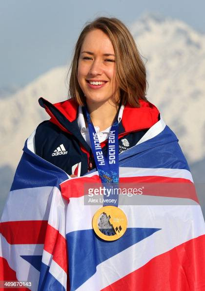 Lizzy Yarnold of Great Britain stands with her gold medal and wrapped in the Union Jack flag after winning the Women's Skelton as she poses for a...